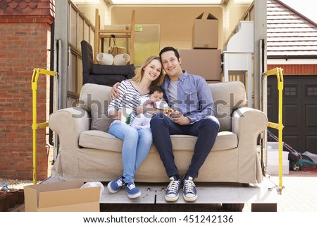 Family With Sofa On Tail Lift Of Removal Truck Moving Home - stock photo