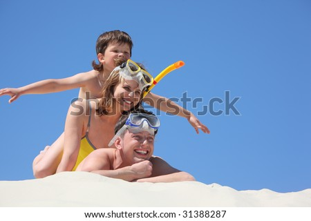 family with son lying on sand with snorkeling masks