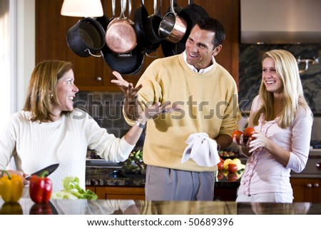 Family with teen girl talking together in kitchen - stock photo