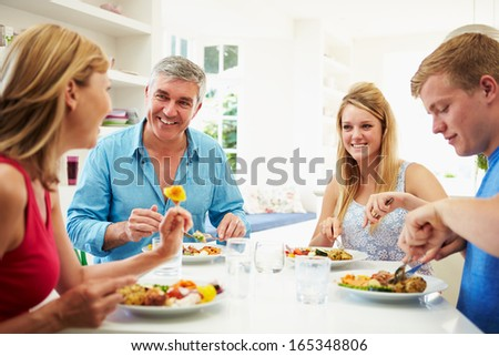 Family With Teenage Children Eating Meal At Home Together - stock photo