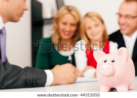 Family with their consultant (assets, money or similar) doing some financial planning - symbolized by a piggy bank in the front (focus only on piggy bank!) - stock photo