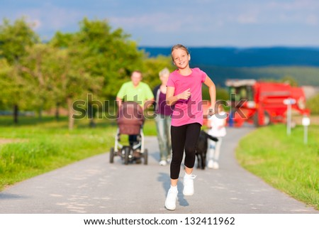 Family with three children, one baby lying in a baby buggy, walking down a path outdoors, two kids are running ahead, there is also a dog - stock photo