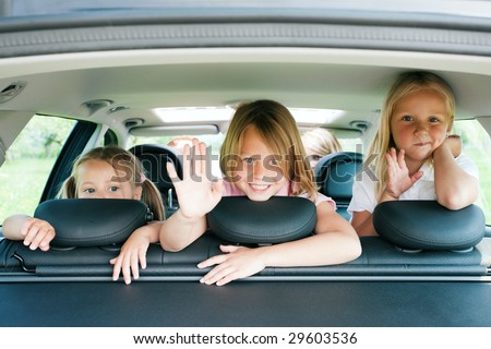 Family with three kids in a car - stock photo