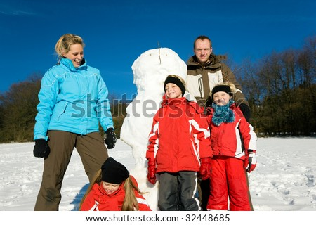 Family with three kids in wintertime standing on front of their newly build snowman - stock photo