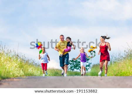 Family with three kids running down a hill in summer - stock photo