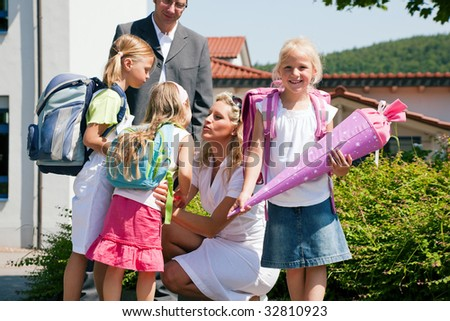 Family with three kids sending them to school - stock photo