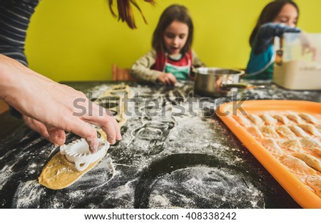 Family with twin girls is making home made pastry dumplings tortellini or ravioli.