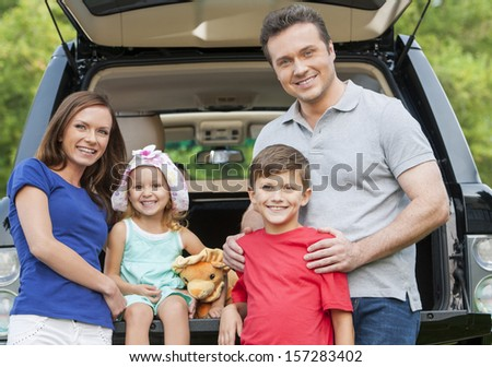 Family with two childre is out for picnic. All are happy and smilling - stock photo