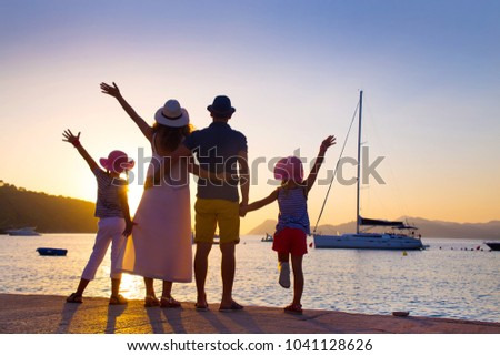 Family with two children admiring the sunset on the sea coast. silhouette.