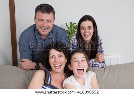 Family with two children at home laughing - stock photo
