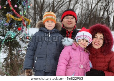 family with two children: father, mother, boy and girl near christmas tree.