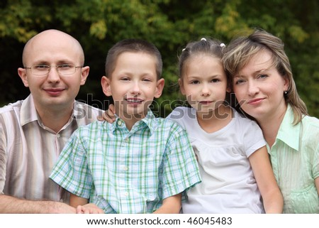 family with two children in early fall park. father, mother, little boy and girl - stock photo