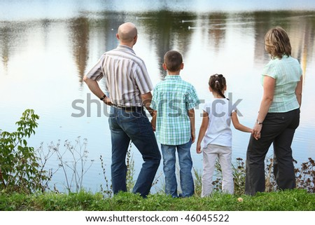 family with two children in early fall park near pond. they are looking at water. - stock photo