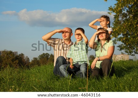 family with two children in early fall park. they sitting on grass and looking at sunset - stock photo