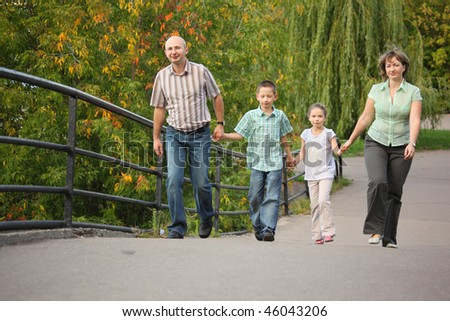 family with two children is handies on a bridge and walking - stock photo