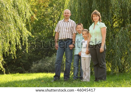 family with two children is standing near osier in early fall park. - stock photo