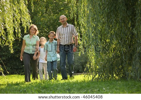 family with two children is walking in early fall park. dad and mom is smiling - stock photo