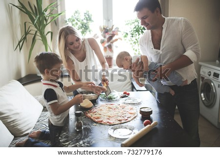 family with two children prepare pizza, add ingredients, in a cozy real kitchen, copy space and lifestyle, selective focus