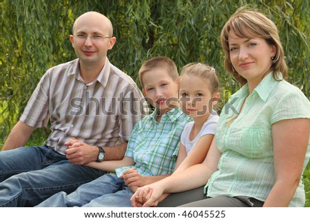 family with two children sitting at the grass in early fall park. focus on little girl's face - stock photo