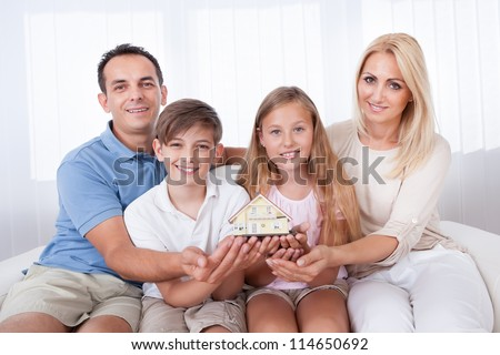 Family With Two Children Sitting On Couch Holding Miniature Model Of House At Home - stock photo