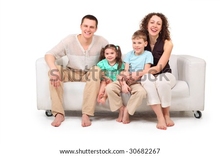Family with two children sitting on white leather sofa