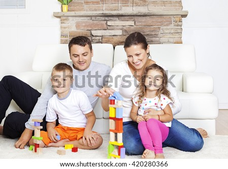 Family with two children, spending time together, playing with building blocks