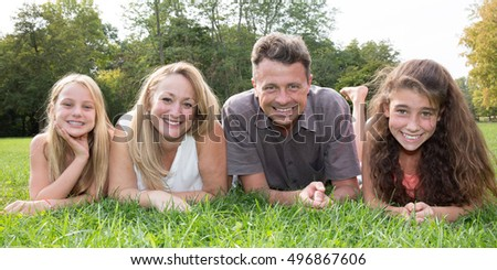 Family with two girls on grass having fun