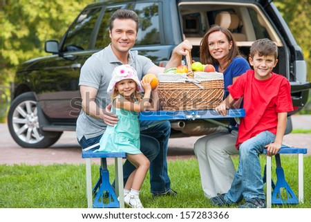 Family with two kids at picnic, sitting together at the table with fruit basket - stock photo