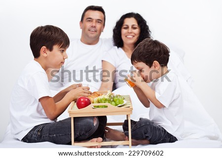 Family with two kids having a healthy breakfast in bed - stock photo