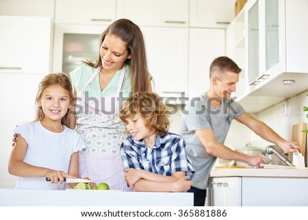 Family with two kids working in kitchen and cutting lime fruits
