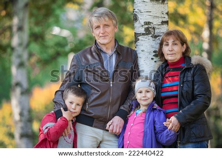 Family with two mature parents and son with daughter standing in park at autumn - stock photo
