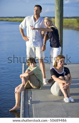 Family with two teenage children on dock by water, father and daughter watching and pointing - stock photo