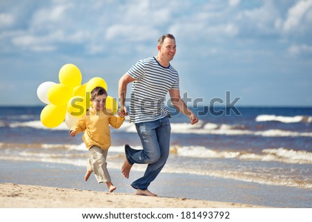 Family with yellow balloons playing on the beach - stock photo