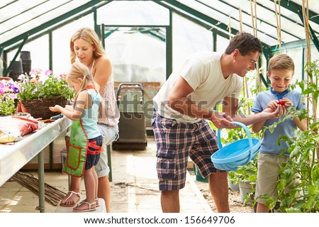 Family Working Together In Greenhouse - stock photo
