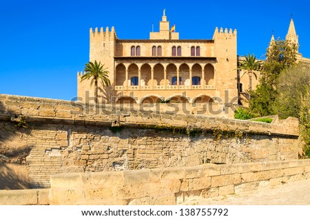 Famous Almudaina Royal Palace palm tree sunny blue sky, Palma de Mallorca, Spain - stock photo