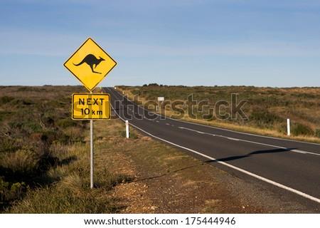 famous Australian Kangaroo road sign along a straight road. - stock photo
