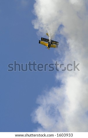 Famous Bulldog stunt biplane, piloted by Jim LeRoy, performing a vertical loop and trailing smoke