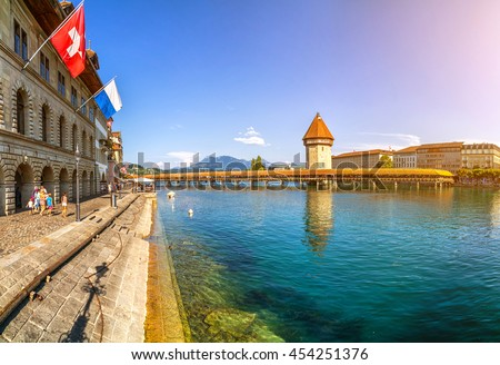 Famous Chapel Bridge in the historic city center of Lucerne, the city's symbol and one of Switzerland's main tourist attractions and views on a sunny day in summer, Canton of Lucerne, Switzerland - stock photo