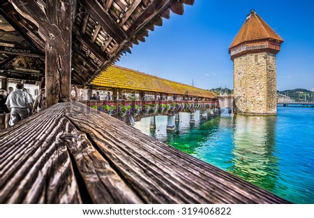 Famous Chapel Bridge in the historic city center of Lucerne with, the city's symbol and one of Switzerland's main tourist attractions and views on a sunny day in summer, Canton of Lucerne, Switzerland - stock photo