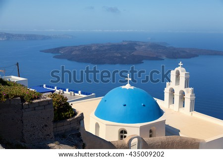 Famous church in Fira, Santorini at daytime. Volcano on background