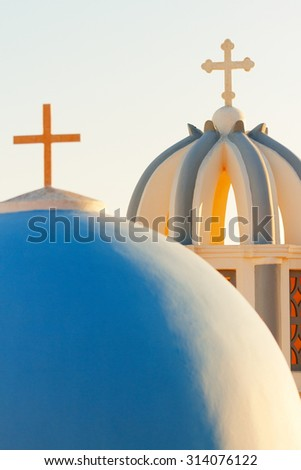Famous church in Fira, Santorini at sunset. Close up on the domes and crosses - stock photo