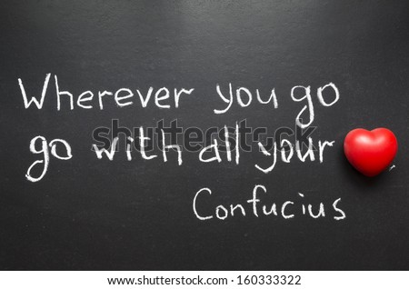 """famous Confucius quote """"Wherever you go, go with all your heart"""" handwritten on blackboard - stock photo"""