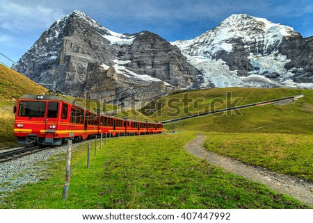 Famous electric red tourist train coming down from the Jungfraujoch station(top of Europe) in Kleine Scheidegg,Bernese Oberland,Switzerland,Europe - stock photo