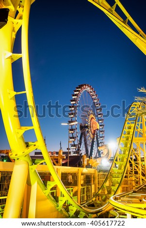 famous ferris wheel and rollercoaster at the oktoberfest in munich - germany - stock photo