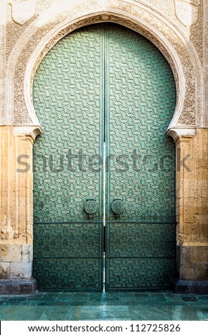 Famous landmark in Spain. Beautiful cathedral Mezquita of Cordoba, Andalucia. Green door with arch in old arabic style. Traditional spanish architecture. Religious and tourist place in Europe. - stock photo