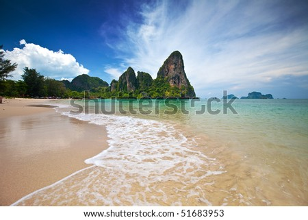 Famous limestone cliffs of Krabi bay overlooking wide sandy beach off west coast of Thailand - stock photo