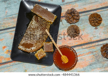 Famous Marmaris (Turkey) pine honey comb and liquid honey on surface imitating wood  with cones. Photo toned