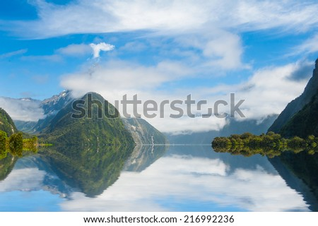 Famous Mitre Peak rising from the Milford Sound fiord and reflecting in water. Fiordland national park, New Zealand - stock photo