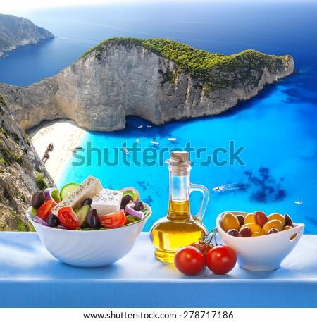 Famous Navagio beach with Greek salad in Zakynthos, Greece - stock photo