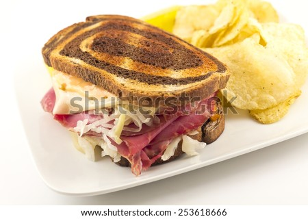 Famous New York Reuben corned beef sandwich with chips and a pickle - stock photo